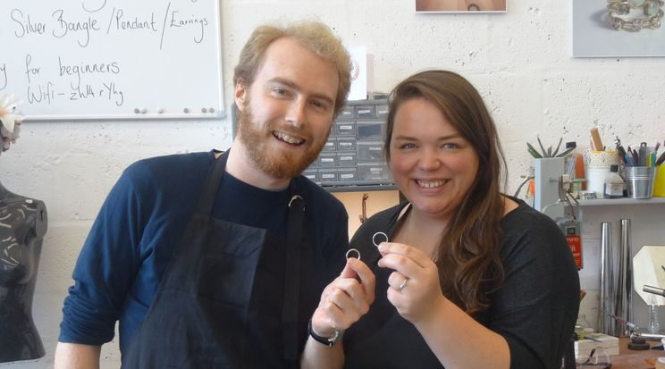 Duncan and Alex holding their rings in a workshop